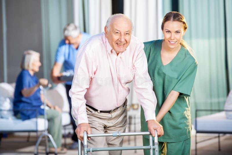 Female Caretaker Helping Senior Man In Using royalty free stock photos