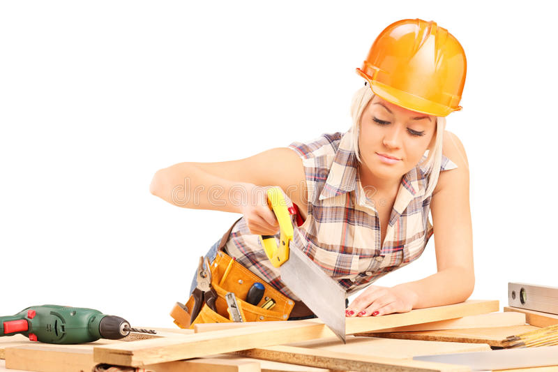Female carpenter cutting plank with a handsaw stock photography