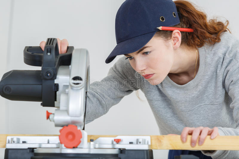 Female carpenter cutting wood with circular power saw royalty free stock photos