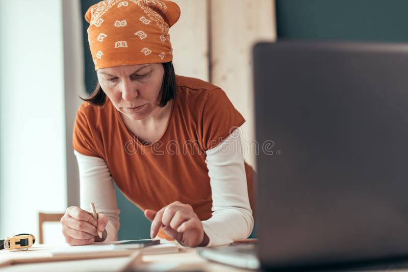 Female carpenter doing financial calculation stock image