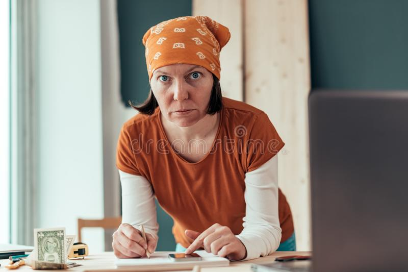 Female carpenter doing financial calculation royalty free stock photography