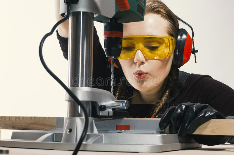 Female carpenter and drilling machine. royalty free stock photography