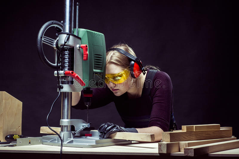 Female carpenter and drilling machine. Beautiful female carpenter at work using vertical drilling machine. Photo on black background stock image