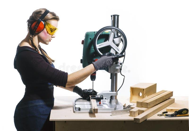 Female carpenter and drilling machine. Beautiful female carpenter at work using vertical drilling machine. Photo on white background royalty free stock photo