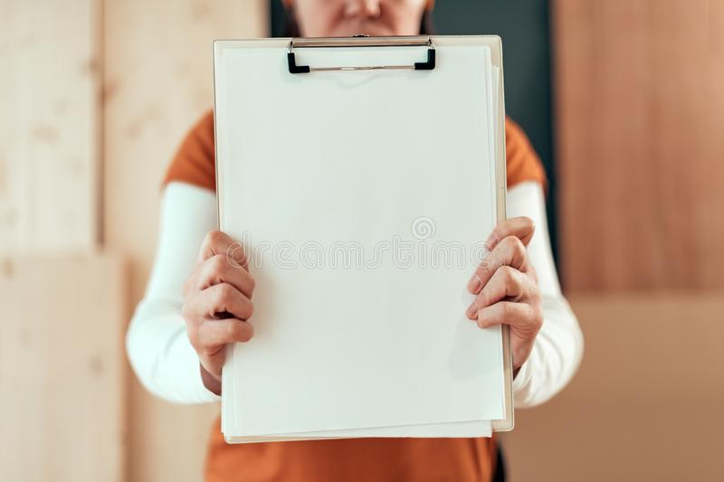 Female carpenter holding clipboard note pad paper mock up stock images