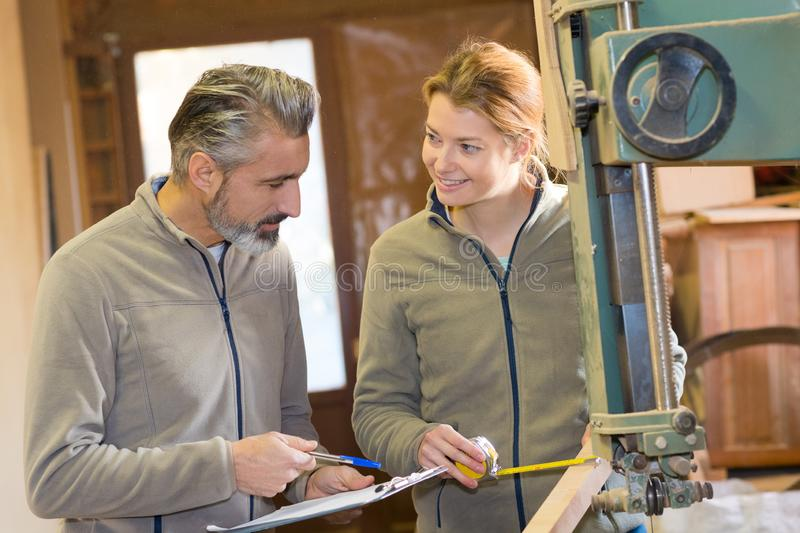 Female carpenter measuring wood colleague taking notes stock photos