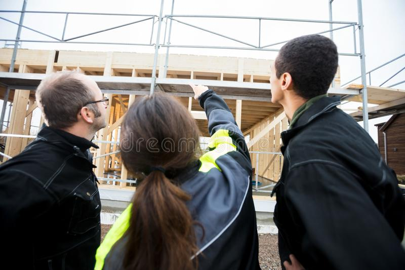 Female Carpenter Pointing Towards Incomplete Building By Colleag. Rear view of female carpenter pointing towards incomplete building while standing by colleagues royalty free stock photography
