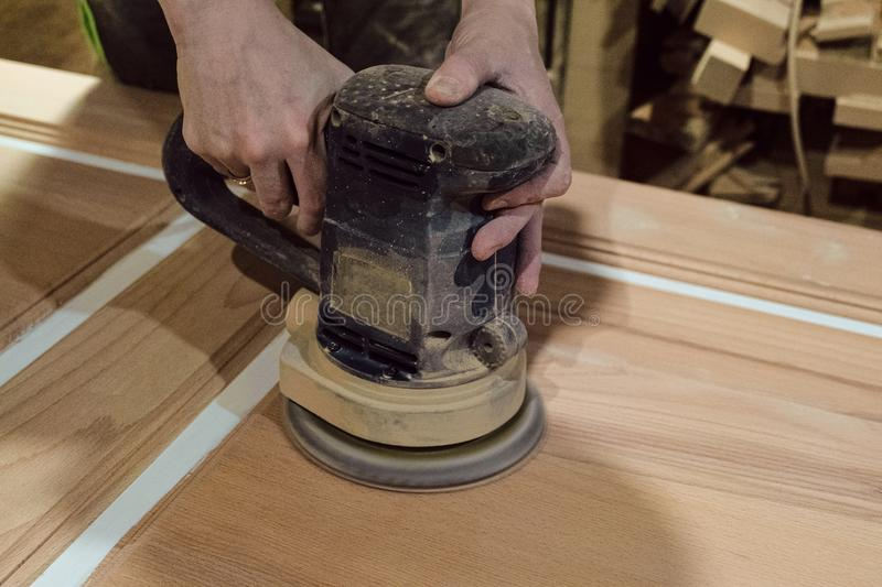 Female carpenter polishes the wooden door surface with electric grinding machine stock photography
