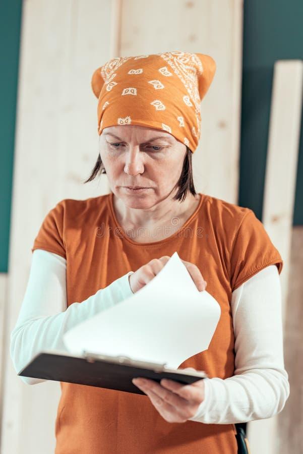 Female carpenter reading DIY project notes stock photos
