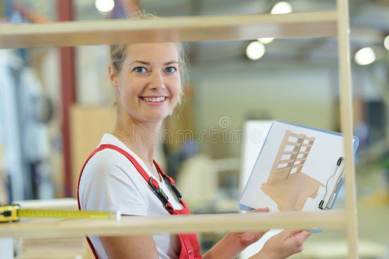 Female carpenter showing design from catalog. Carpenter stock photo