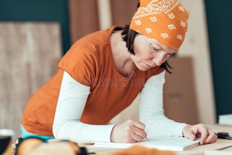 Female carpenter sketching project draft notes in woodwork workshop. Female carpenter wearing bandanna is sketching project draft on clipboard note paper in her royalty free stock image