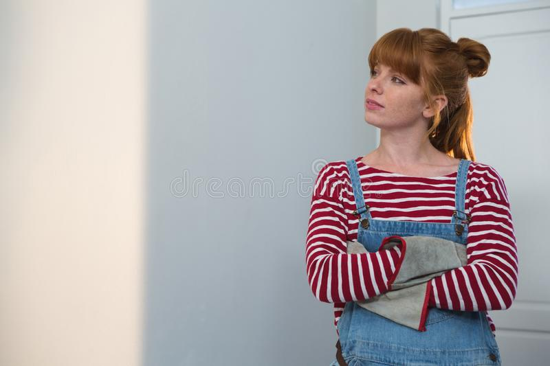 Female carpenter standing with arms crossed stock photography