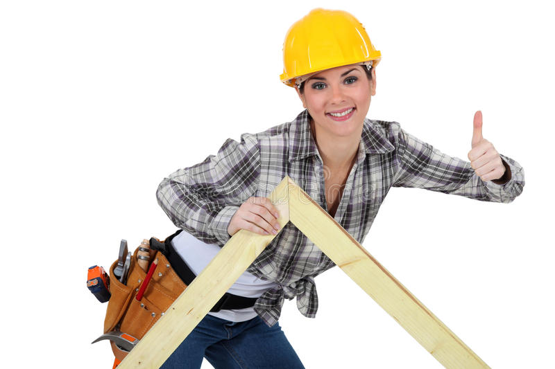 Female carpenter with truss. Female carpenter with a wooden truss stock images