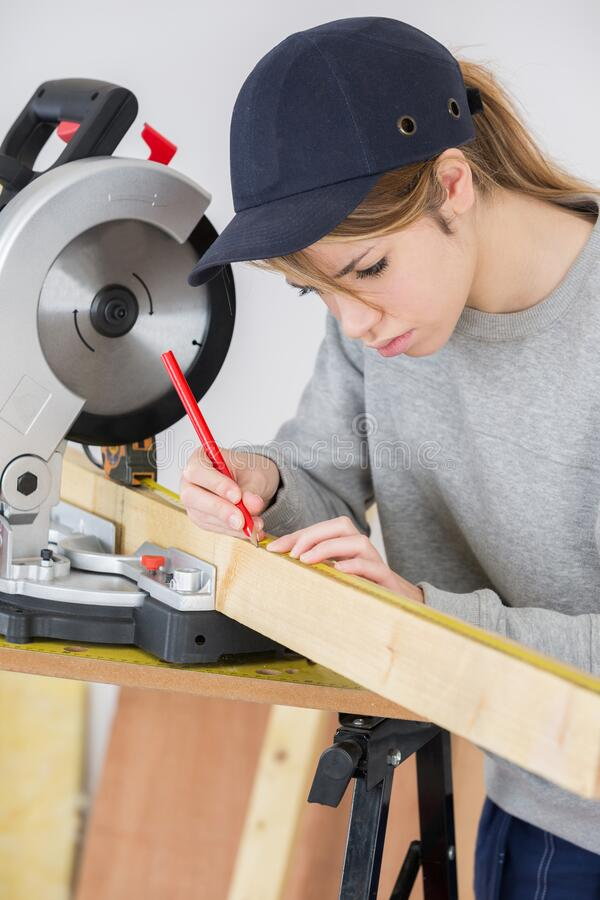 Female carpenter using circular saw royalty free stock images