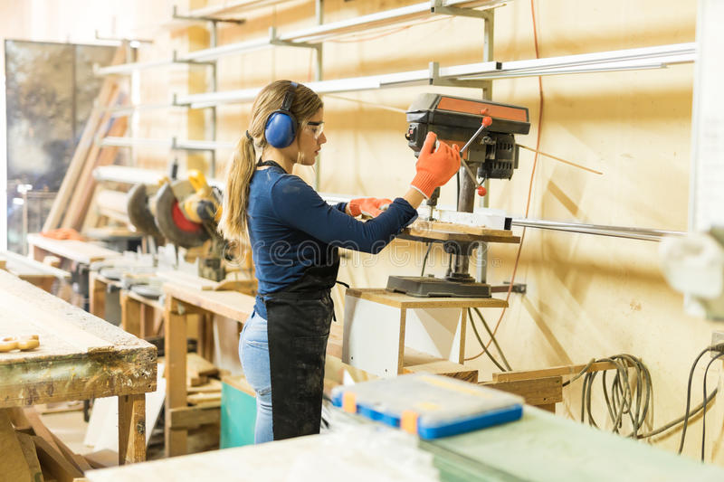 Female carpenter using a drill press stock photo
