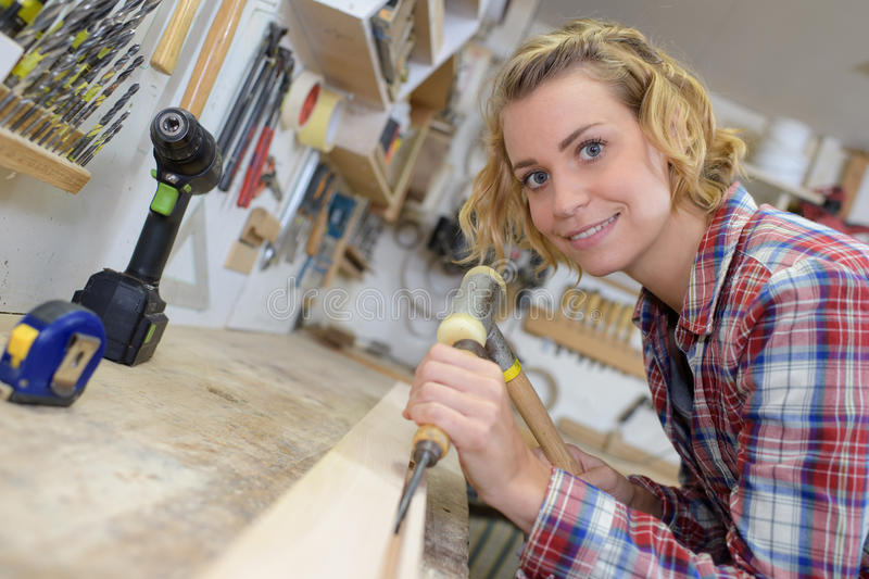 Female carpenter working with hammer and chisel in workshop. Female carpenter working with a hammer and chisel in workshop stock image