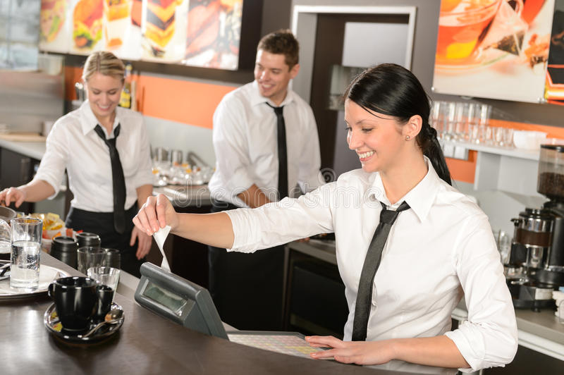 Female cashier giving receipt working in cafe. Female cashier giving receipt colleagues working in cafe stock photography