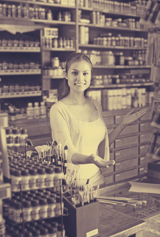 Female cashier standing in art shop stock image