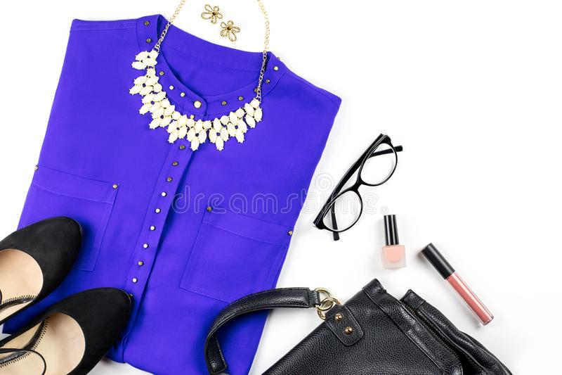 Female casual office style clothing and accessories -purple shirt, heeled shoes, handbag, make up items. royalty free stock photos
