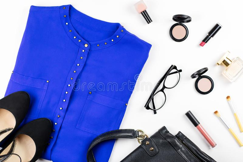 Female casual office style clothing and accessories -purple shirt, heeled shoes, handbag, make up items. Top view stock images