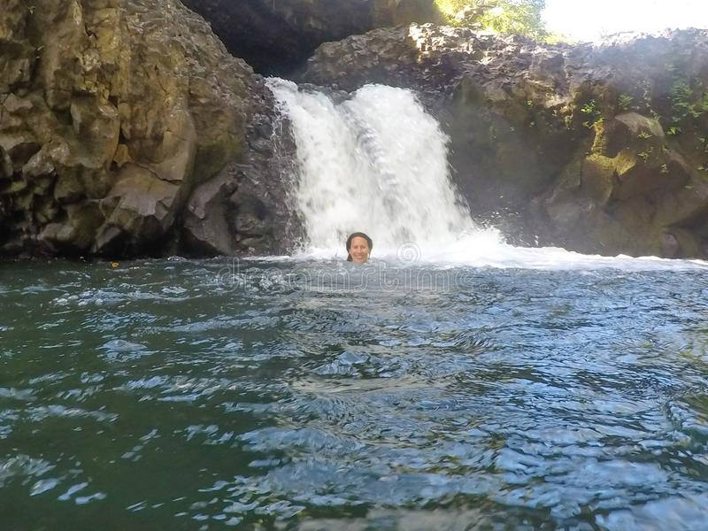 Female caucasian tourist swimming in water at Togitogiga Waterfall on Upolu Island, Samoa, South Pacific. Female caucasian tourist smiling and swimming in water royalty free stock photography