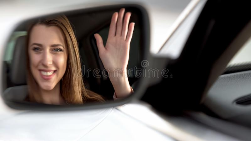 Female celebrity sitting in vehicle and waving hand, rearview mirror reflection royalty free stock photography