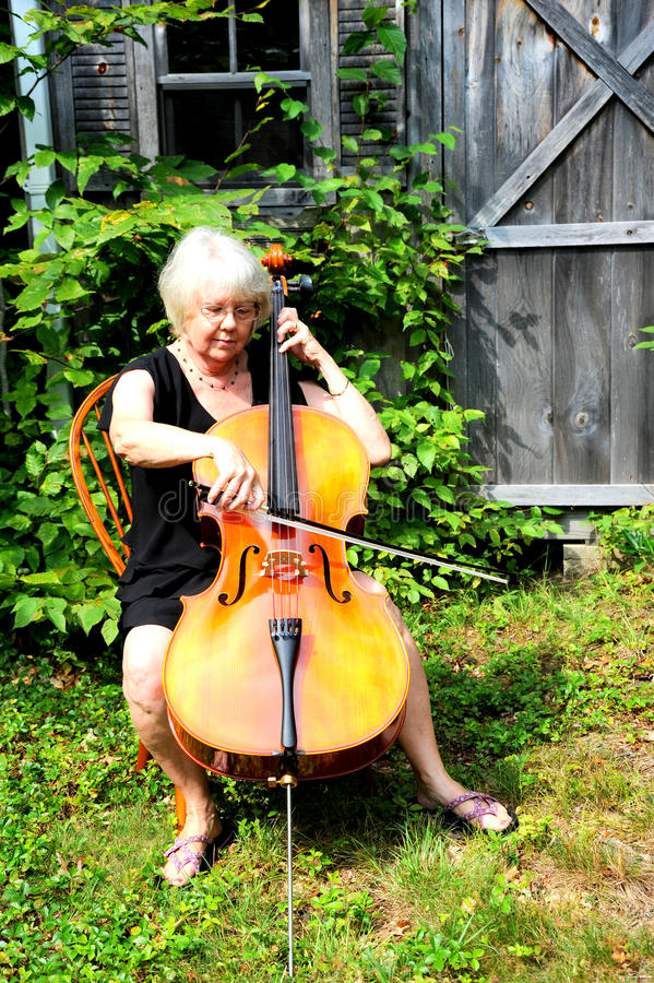 Female cellist. Female cellist performing classical music outdoors stock photography