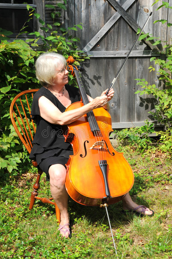 Female cellist. Female cellist performing classical music outdoors royalty free stock photos