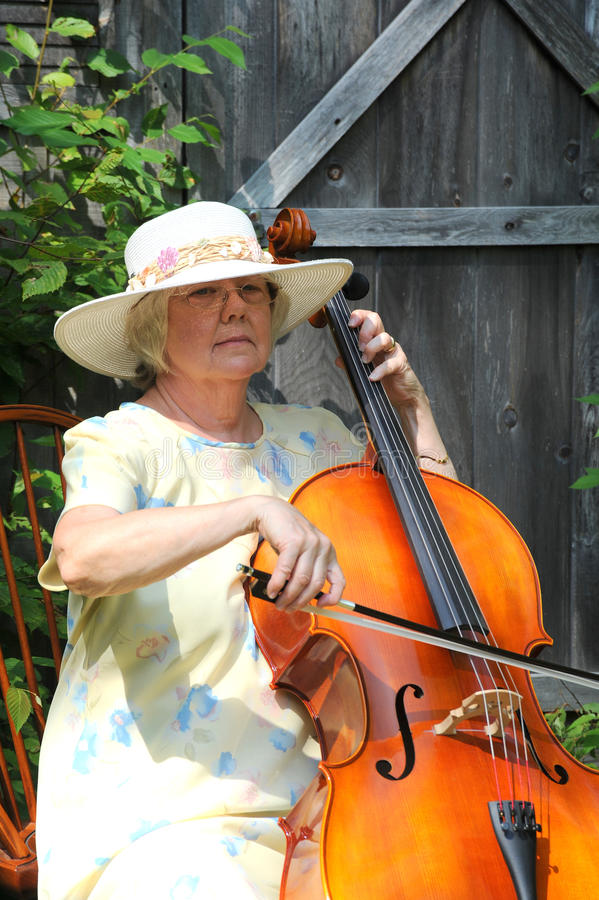 Female cellist. Female cellist performing classical music outdoors royalty free stock images