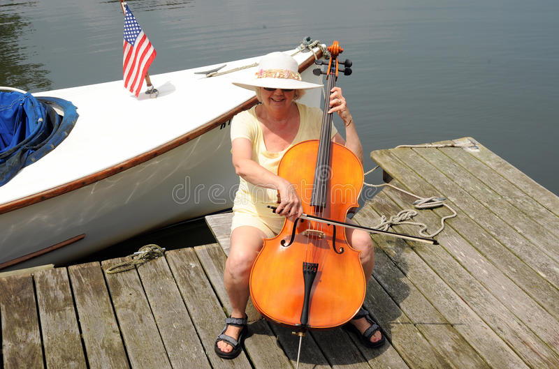 Female cellist. Concert by the lake with a female cellist royalty free stock images