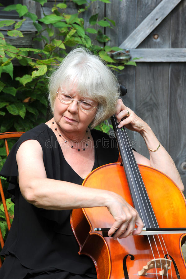 Female cellist. Performing on her instrumant outside stock image