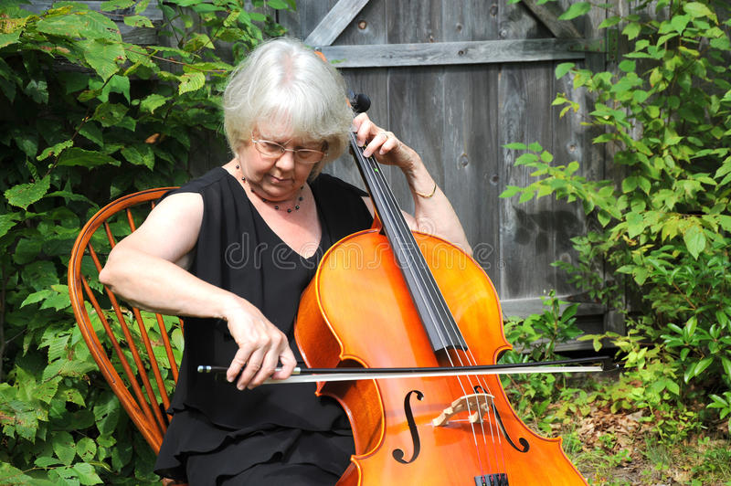 Female cellist. Performing on her instrumant outside royalty free stock images