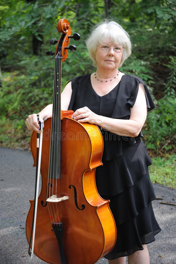 Female cellist. Female cellist music teacher standing with her cello outside royalty free stock photos