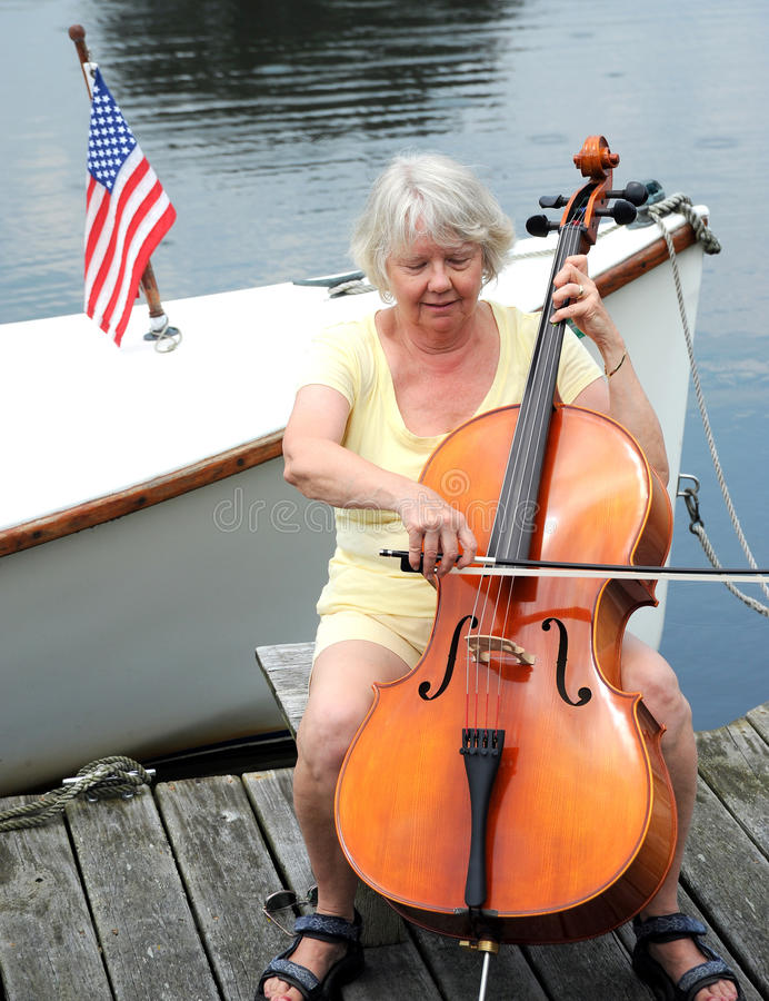 Female cellist. Female cellist performing a classical solo on the pier of a lake royalty free stock images