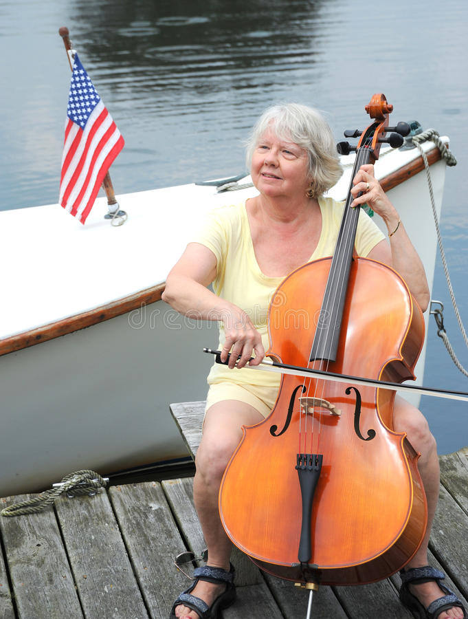 Female cellist. Female cellist performing a classical solo on the pier of a lake stock photos
