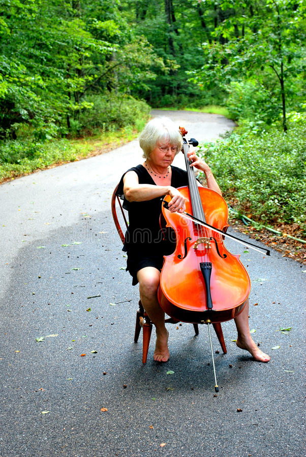 Female cellist. Female cellist with her cello outside stock photo