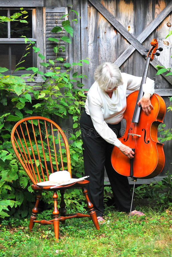 Female cellist. Female cellist posing with her instrument outdoors royalty free stock photo