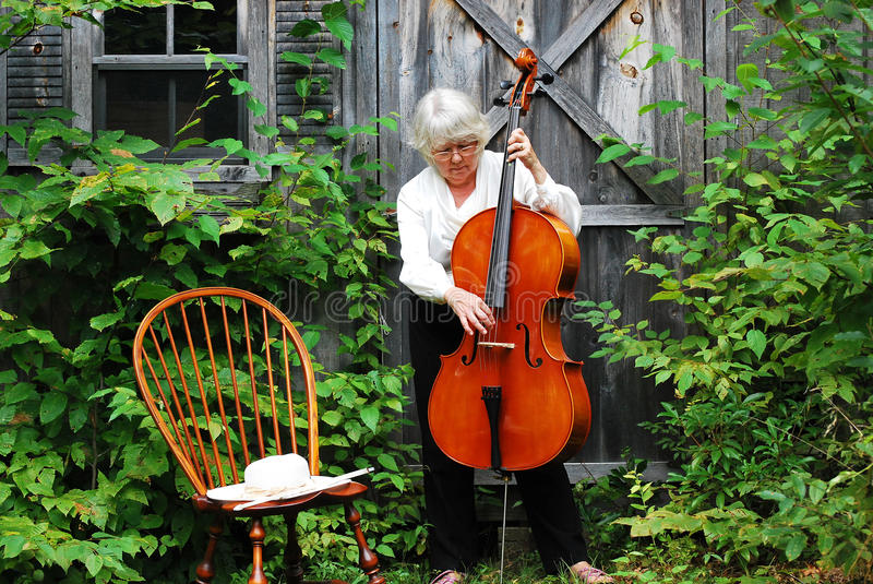 Female cellist. Female cellist posing with her instrument outdoors royalty free stock photos