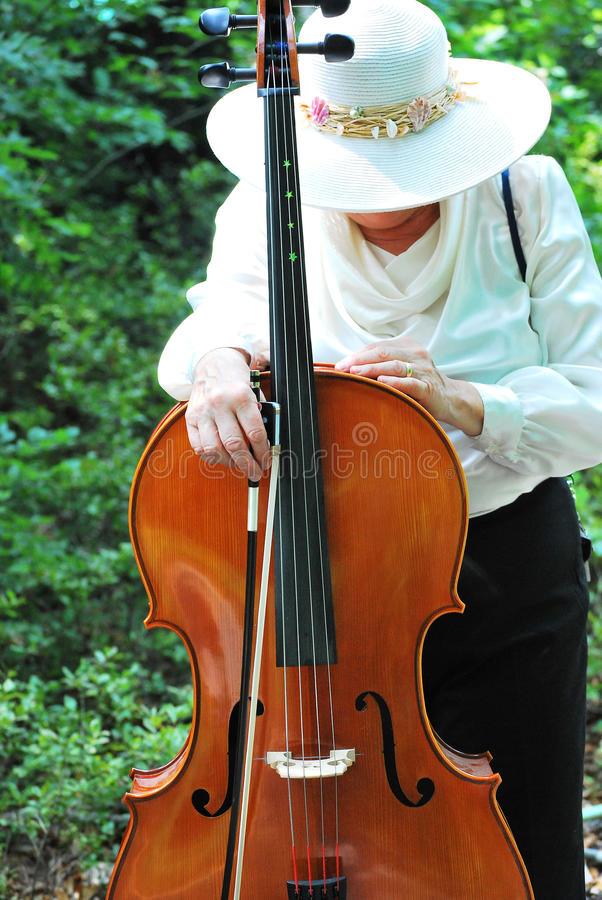 Female cellist. Mature female cellist with her cello outside royalty free stock photography