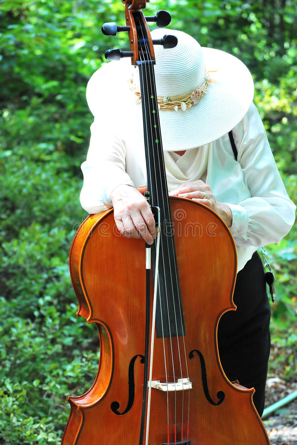Female cellist expressions. Mature female cellist expressions outside stock photos