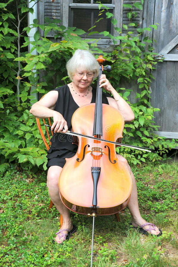 Female cellist. Mature female cellist with her instrument outside royalty free stock photos