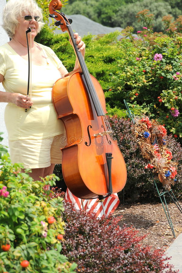 Female cellist. Mature female cellist with her instrument outside stock images
