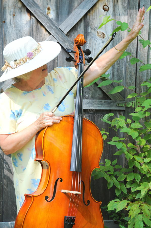 Female cellist. Mature female cellist with her instrument outside stock photo