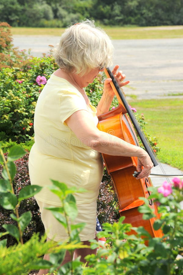 Female cellist. Mature female cellist with her instrument outside stock image