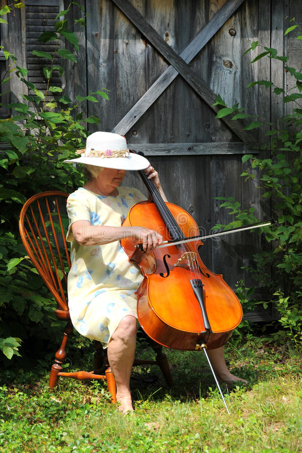 Female cellist. Mature female cellist performing a classical solo outside royalty free stock photo