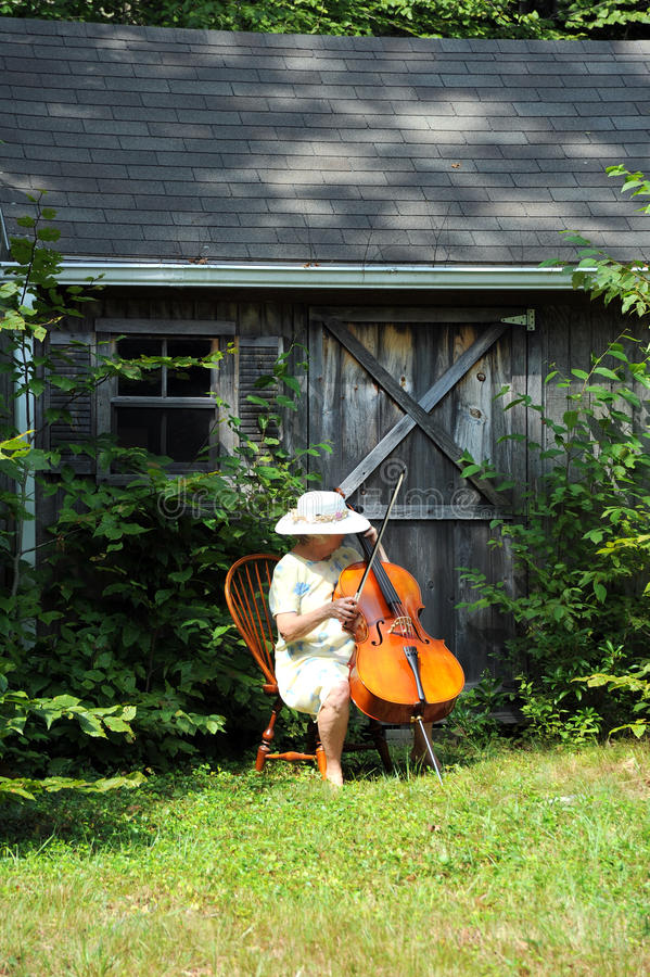 Female cellist. Mature female cellist performing a classical solo outside royalty free stock photography