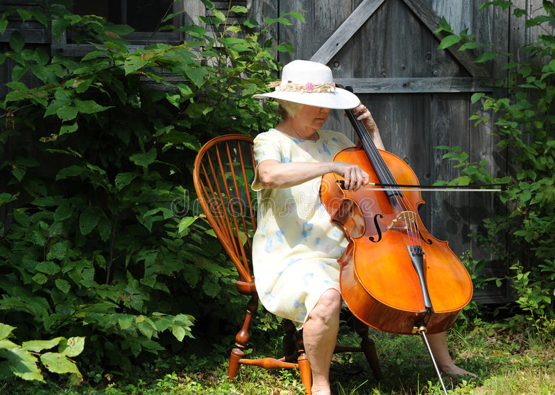 Female cellist. Mature female cellist performing a classical solo outside stock image