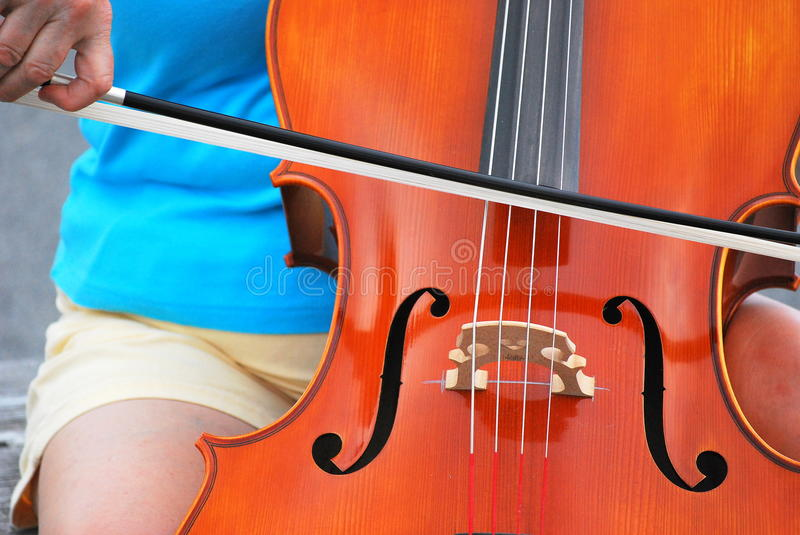 Female cellist. Mature female cellist performing in concert outside royalty free stock image