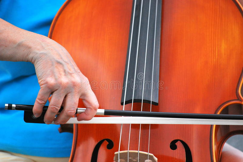 Female cellist. Mature female cellist performing in concert outside stock photo
