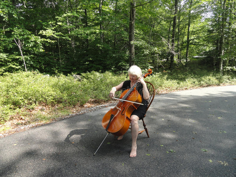Female cellist. Female cellist performing a classical solo outside royalty free stock images